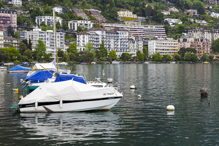 MONTREUX, SWITZERLAND - MAY 26, 2013: Boats moored in the waters of Lake Geneva. Along the coastline on the slope of a hill the landscape of the city can be seen Editorial