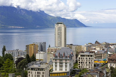 montreux: MONTREUX, SWITZERLAND - MAY 30, 2013: Cityscape and in the middle only one skyscraper it is seen from above complemented overlooking forested mountains on the other shore of Lake Geneva