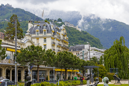 tu puedes: MONTREUX, SWITZERLAND - MAY 26, 2013: Fabulous building with yellow awnings and the hills on which in the distance you can see the other buildings. More distant hill is covered with snow and fog