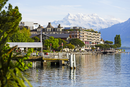 montreux: MONTREUX, SWITZERLAND - MAY 27, 2013: Ferry Terminal on lake , lots of greenery, nice architecture, high snow-capped peaks and promenade by the lake shows the diversity of attractions for visitors Editorial