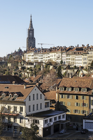 BERN, SWITZERLAND - DECEMBER 26, 2015: General view towards facades of the city together with a high church tower shows a significant density of development of the Old Town