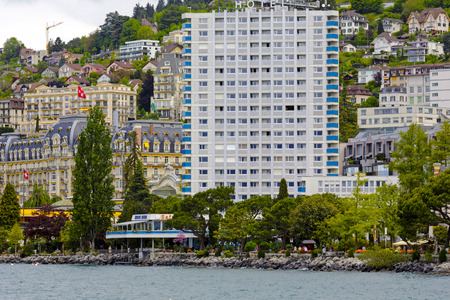 MONTREUX, SWITZERLAND - MAY 20, 2013: High building on the shore of Lake Geneva together with houses that are visible in the background it creates landscape of a city looked like is densely built-up Redakční