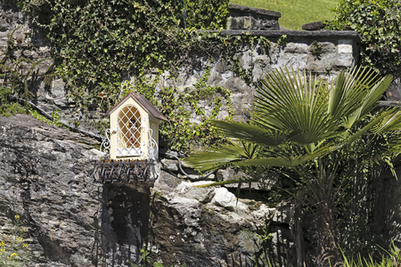 sacral: WEGGIS, SWITZERLAND - MAY 05, 2016: The tiny chapel is located on a rock under a stone fence in the vicinity of various plants. The origin of this tiny sacral architecture is not widely known.