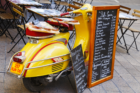 Nice, France - May 18, 2014: Vespa scooter parked on a sidewalk next to the outdoor seating restaurant is used as a stand to showcase the current menus Editorial