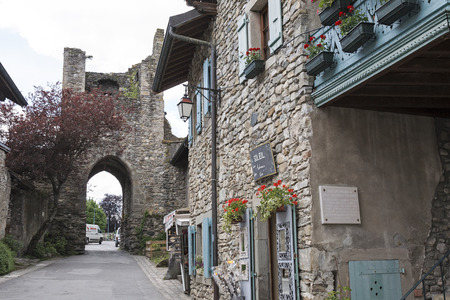 townhouses: Yvoire, France - May 24, 2013: Narrow street leads through a gate in the damaged tower. Townhouses which were built of stone can be seen in this medieval town. Editorial