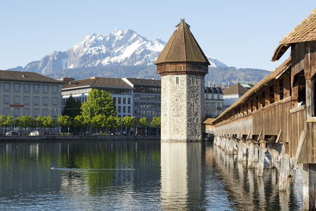 octogonal: Lucerne, Switzerland - May 05, 2016: Octagonal tower and the Roofed Chapel Bridge by the River Reuss. Peak of Pilatus that is covered with snow can be seen in the distance