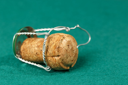 uncork: Cork of a sparkling wine  is shown on a green background
