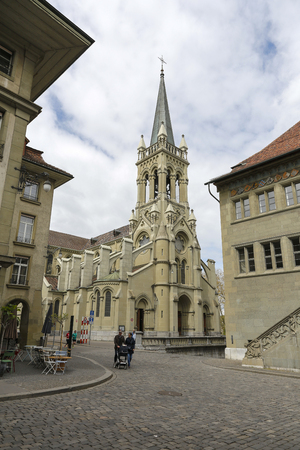 Bern, Switzerland - April 17, 2017: Church of Sts. Peter and Paul is a Christian Catholic church that can be seen among other urban buildings and on the cobbled street are people in the distance Sajtókép