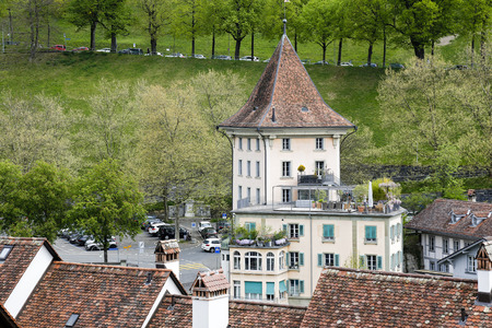 Bern, Switzerland - April 17, 2017: Residential building and its part which looks like a tower covered with sloping roof dominates in the green landscape of the city