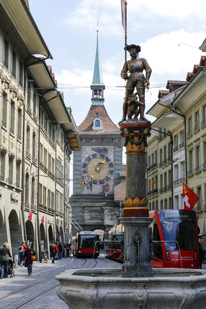 Bern, Switzerland - April 20, 2017: Traffic on the street surrounded by monuments such as the Clock Tower named Zytglogge and a fountain called Musketeer (Schutzenbrunnen)