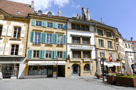 Yverdon-les-Bains, Switzerland - 18 April 2017: Variety of colorful townhouses near the city square. There are several store fronts on the ground floor