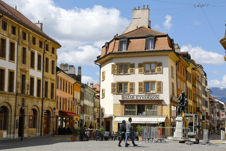 Yverdon-les-Bains, Switzerland - 18 April 2017: Various tenements in the old town. Monument, a sidewalk cafe, several people and repair works on the road can be seen