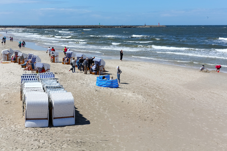 Kolobrzeg, Poland - June 16, 2017: There are a few people uses of roofed beach chairs by the coast. Waves on the surface of the sea are evidence of the windy weather