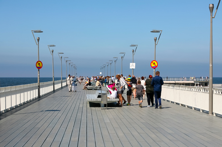 Kolobrzeg, Poland - June 18, 2017: Contemporary modern pier built over the waters of the Baltic Sea in this version exist since 2014. There are people who walk the pier and enjoy the view.