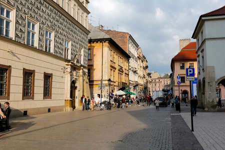 Krakow, Poland - May 25, 2017: Street view in old town is seen in a light of evening sun. There are historic tenement houses, cars, people and the city life can be seen