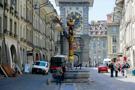Bern, Switzerland - April 20, 2017: The east front of the Clock Tower and  a fountain are  located at the end of the Kramgasse in Old City and both are one of the most recognizable sights of the city
