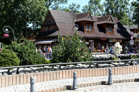 Zakopane, Poland - August 08, 2017: Traditional building at Krupowki, formerly residential building which is commercial building now. People walking along the street can be seen