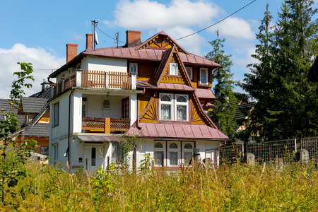 Zakopane, Poland - August 08, 2017: Villa that is named The Cyganeczka was built approx. 1927 year and this is partly of wood and partly of brick. This house is seen among grasses and trees