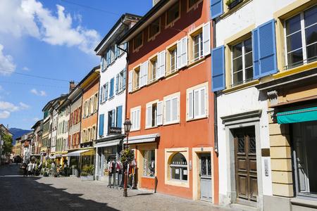 Yverdon-les-Bains, Zwitserland - 18 april 2017: Kleurrijke huurkazernes en hun kleurrijke luiken sieren een kleine straat in de oude stad. Er zijn verschillende winkelpuien op de begane grond.