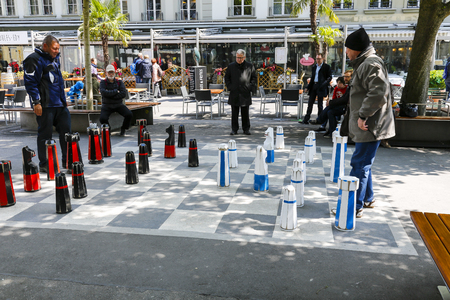 Bern, Switzerland - April 20, 2017: Street photography shows men playing chess in the city on a chessboard painted on the pavement. There are also interested observers of this game.