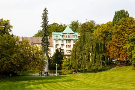マリアンスケ・ラズネ、チェコ共和国 - 9月 09, 2017: 彼らは少し遠くに見える長屋をカバーしたいかのように、わずかに秋の色の公園の木々