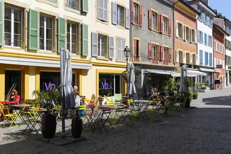 Yverdon-les-Bains, Switzerland - 18 April 2017: Tea Room and its outdoor tables and chairs. It is seen in the narrow street and there are a few people