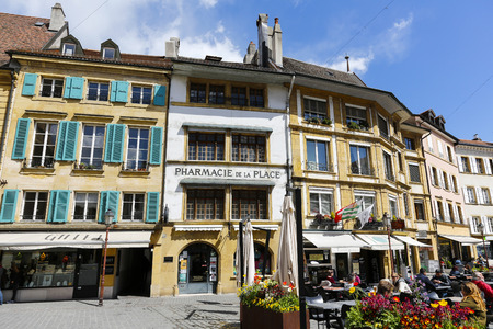 Yverdon-les-Bains, Switzerland - 18 April 2017: Tenement houses by the town square. On the side, among the flowers there is a small outdoor restaurant and several people are there.