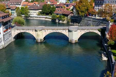 Bern, Switzerland - September 25, 2017: The old stone bridge, which for pedestrians and vehicles connects the banks of the Aare River, is seen in the surroundings of traditional residential houses.