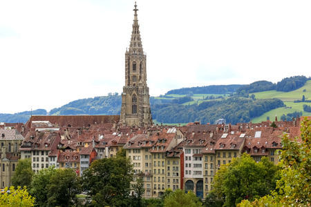 Bern, Switzerland - September 18, 2017: The tower of the cathedral dominates over other residential buildings of the old town. In the distance there are meadows and forests on the hill.