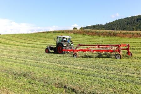 Bern, Switzerland - September 16, 2017: The tractor and its accessories are on the field. The agricultural machinery is visible during the work. Editorial