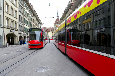 Bern, Switzerland - September 18, 2017: Two trams are on the street in the old part of the city. There are few people in the vicinity. Editorial