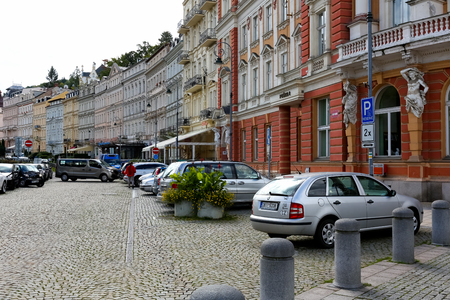 Karlovy Vary, Tsjechië - 11 september 2017: De kleurrijke huurkazernes zijn versierd met veel architectonische details en kunnen worden bekeken door een straat waar meerdere auto's geparkeerd staan Redactioneel
