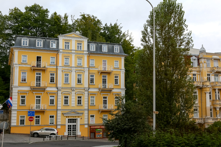 Marianske Lazne, Czechia - September 10, 2017: A beautiful tenement house that looks like a newly renovated building. The yellow facade, small balconies and windows make it worth to stop and to see it