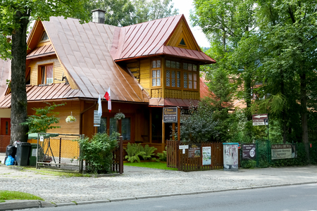 Zakopane, Poland - August 15, 2017: Wooden house with a steep roof, which was covered with painted metal sheets. This villa is located behind the fence by the street and among trees
