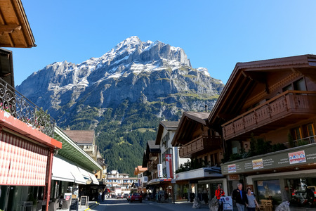 Grindelwald, Switzerland - 21 September 2017: Alpine village and the huge massive rocky mountain dominates over the resort. This view can be admired from the main street. Editorial