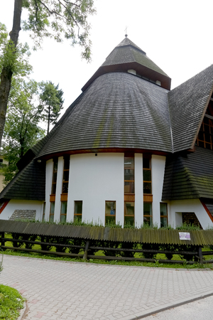 Zakopane, Poland - August 15, 2017: Church with a steep and slopping roof. It is the Church of Divine Mercy that built in 1994 and is seen on a cloudy day.