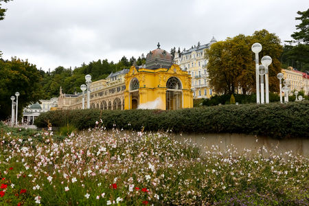Marianske Lazne, Czechia - September 12, 2017: Colonnade behind the garden and park. There are many plants and flowers that beautify the already beautiful architecture of the city anyway. 新聞圖片