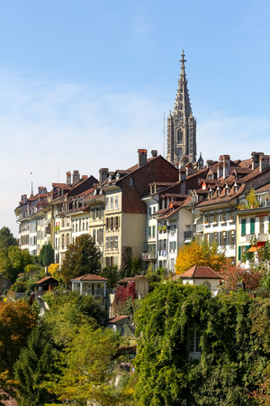 Bern, Switzerland - September 25, 2017: The cathedral tower dominates over other historic buildings of the old town and there is a lot of vegetation below. Editorial