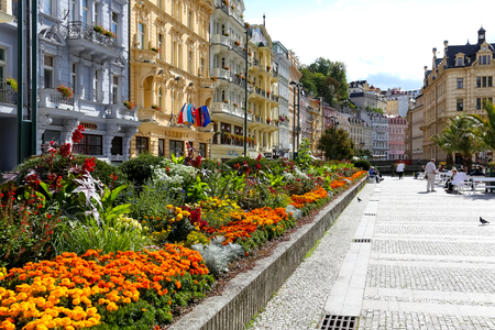 Karlovy Vary, Czechia - September 11, 2017: Flowers by the promenade and row of colorful tenement houses creates a wonderful place of rest for many residents and spa guests who visit this resort Editorial