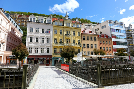 Karlovy Vary, Czechia - September 11, 2017: Footbridge which connects the two banks of the river Tepla leads towards colourful tenement houses being one of the architectural attractions of this resort