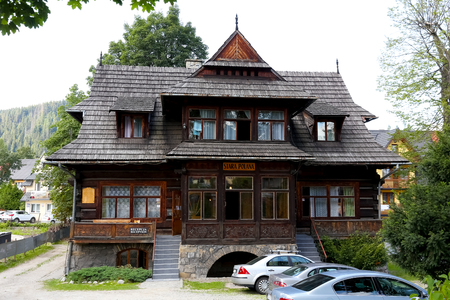 Zakopane, Poland - August 15, 2017: Front view of a wooden log house, which dates back to 1905 and is now known as the Stara Polana, formerly Plazowka. There are several cars in front of the building.