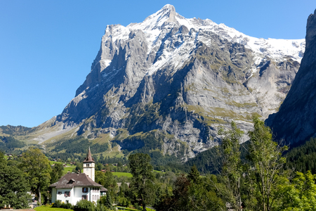 Grindelwald, Switzerland - 21 September 2017: At the foot of a huge rocky mountain called Wetterhorn somewhere on the edge of the village among trees there is a small church and its tower.