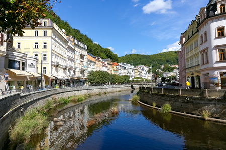 Karlovy Vary, Czechia - September 11, 2017: The River Tepla flows through this magnificent city, full of colourful tenement houses and there are surrounding forests are visible in the distant.
