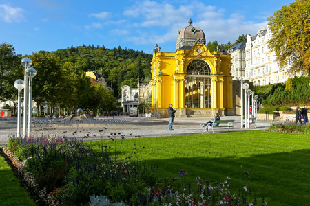 Marianske Lazne, Czechia - September 12, 2017: The public park with its pearls such as the beautiful yellow colonnade building and the fascinating singing fountain are seen in the afternoon sunlight.