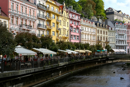 Karlovy Vary, Czechia - September 11, 2017: Colourful tenement houses, many trees and many restaurants are located outdoors and along the banks of the river Tepla.