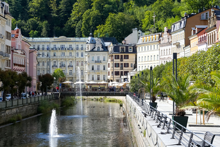 Karlovy Vary, Czechia - September 11, 2017: Tepla River flows through the city along beautiful tenement houses, giving them a lot of tourist attractions. The Grandhotel Pupp in a distance can be seen Editorial