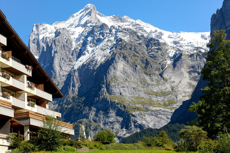 Grindelwald, Switzerland - 21 September 2017: The neighborhood of the apartment building with a huge rocky mountain shows the proximity of this resort with the highest peaks of these great mountains. 에디토리얼