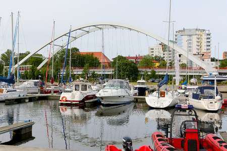 Kolobrzeg, Poland - June 15, 2017: The modern bridge dominates over the marina. Several sailboats are moored at the pier.