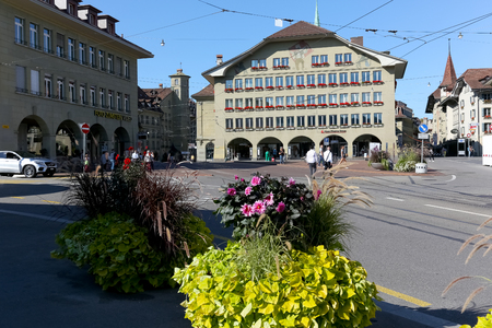 Bern, Switzerland - September 24, 2017: The large edifice with many windows is an example of the traditional architecture that embellishes this magnificent city. There are many flowers in the area.