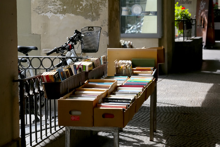 Bern, Switzerland - September 18, 2017: Colorful books in cardboard boxes have been put up for sale. This can be seen along the walkway in the arcades, the seller thus protects the goods from the sun.